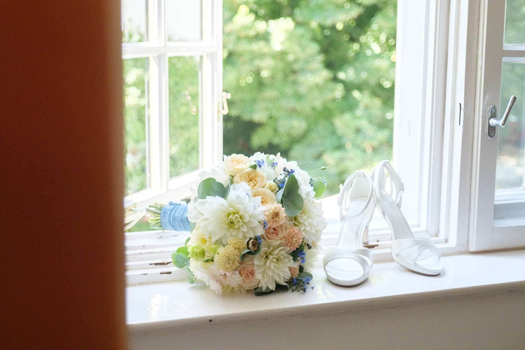 Braut Details mit Strauß und Schuhen vor offenem Fenster