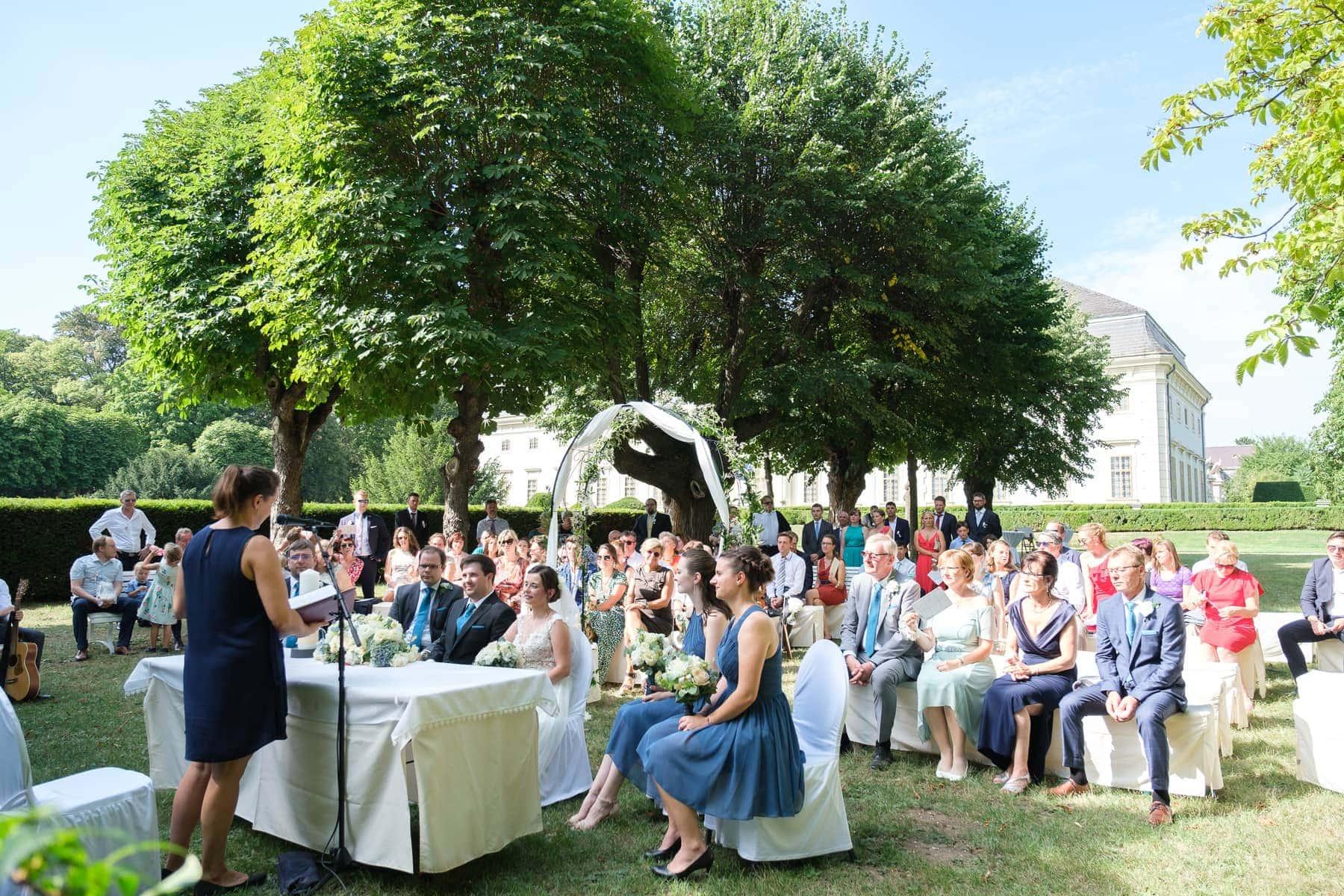 Hochzeitsgesellschaft im Grünen vor Schloss