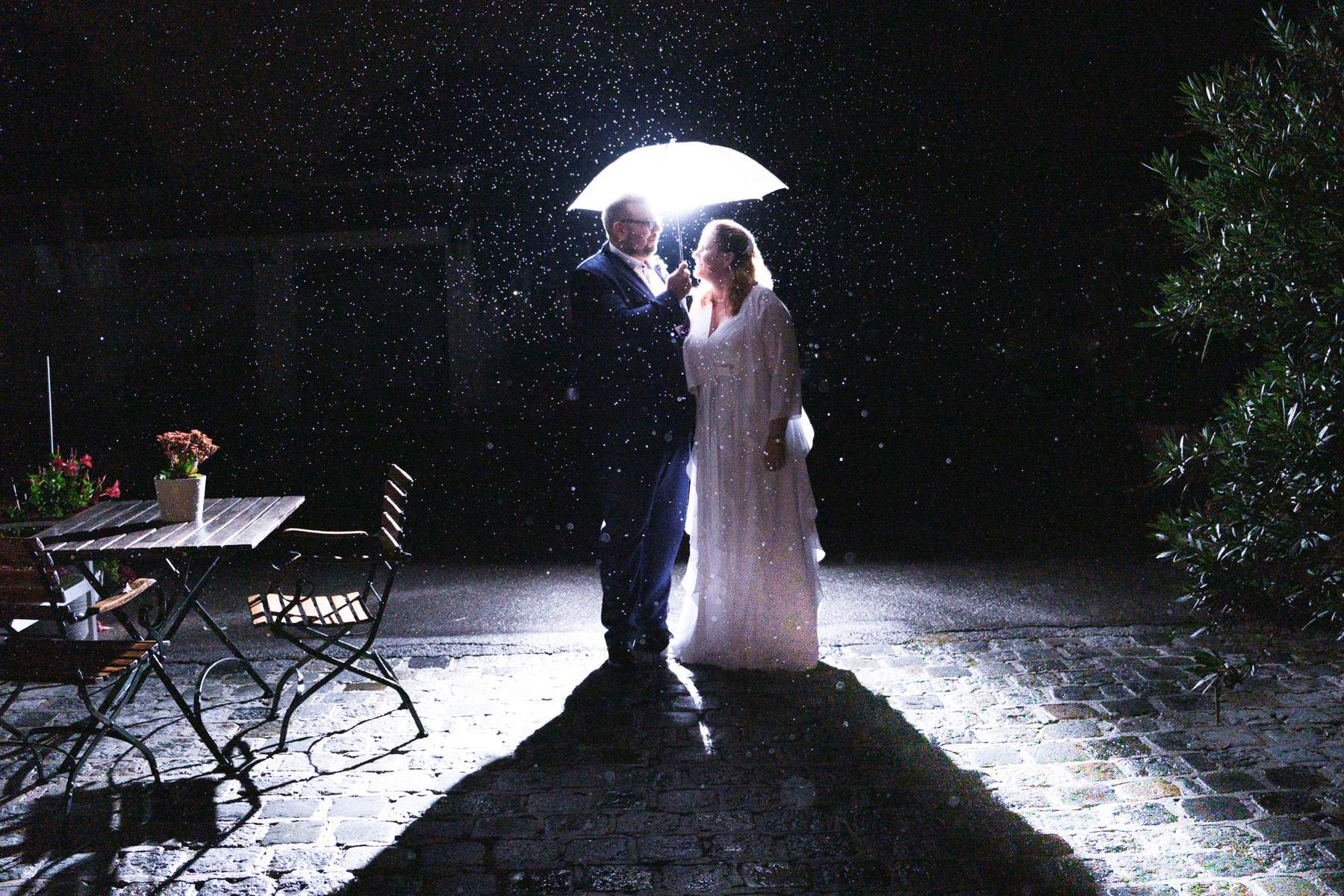 Brautpaar im Regen in der Nacht mit Schirm