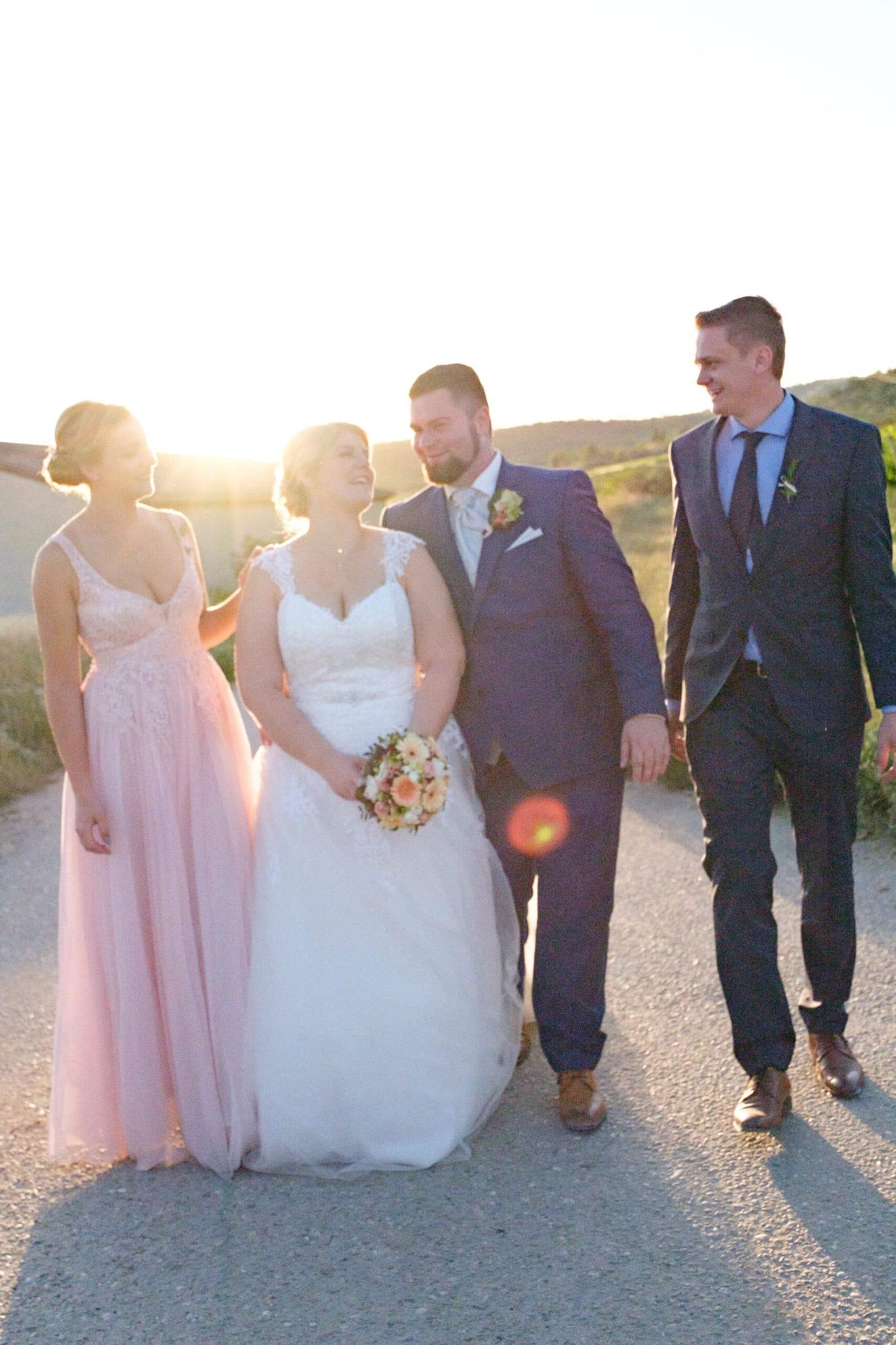 lachendes Brautpaar mit Trauzeugen und Gegenlicht Sonne